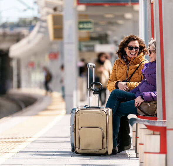 Mature women friends traveler sitting with luggage at train station. Travel concept