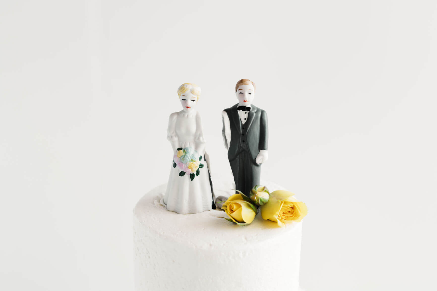 A broken couple standing on their white wedding cake to signify divorce.